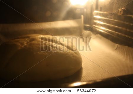 Raw loaf inside an preheated lighted oven.