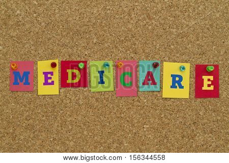 Medicare word written on colorful sticky notes pinned on cork board.