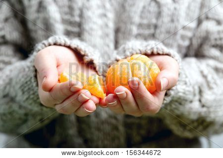 Female hands holding ripe mandarins close up