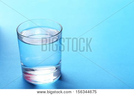 Glass with water on blue background, close up