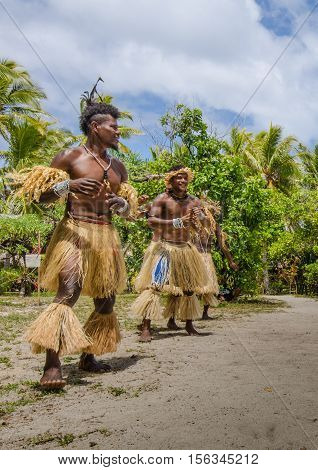 MYSTERY ISLAND - VANUATU OCTOBER 28, 2016: Male dancers in traditional native costumes made from grass entertain visitors from cruise ship spending the day on the uninhabited island.