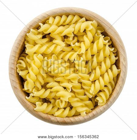 A portion of Rotini corkscrew pasta in wooden bowl. Uncooked dried durum wheat semolina pasta. Isolated on white background