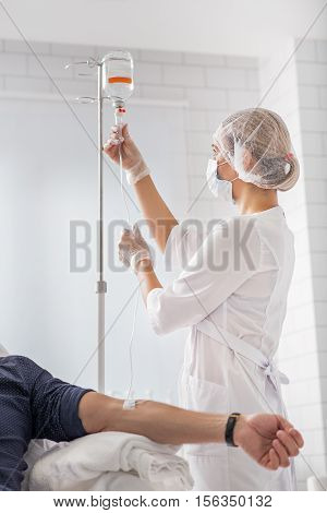 Professional doctor is putting drip for patient. She is standing and looking at medical liquid with seriousness