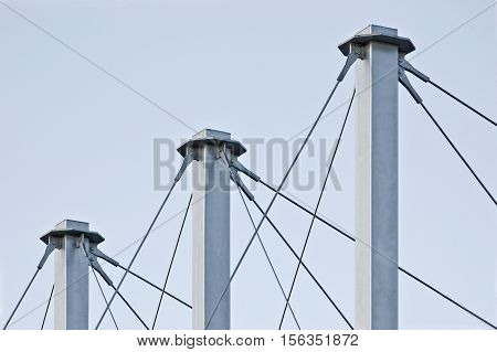 Tied Suspension Roof Cables, Three Tall Grey Masts, Cable-suspended Swooping Rooftop Pylon Anchors, Pale Blue Summer Sky, Large Detailed Horizontal Closeup, Contemporary Construction Concept