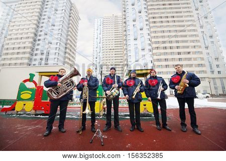 Brass band of six musicians pose on playground near buildings at winter day
