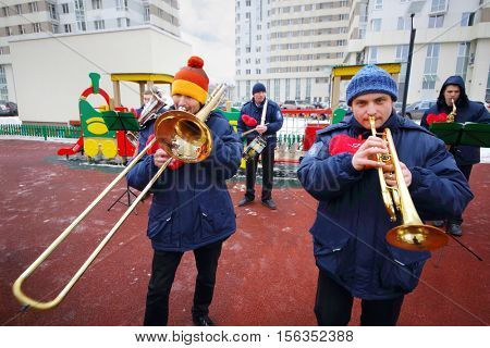 Brass band of five musicians play near building on playground at winter day