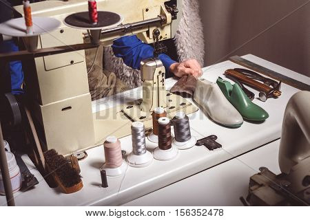 sewing machine with thread reels and a man preparing to sew, close up