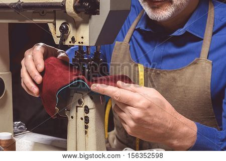 process of stitching pieces of boots by the sewing machine, close up