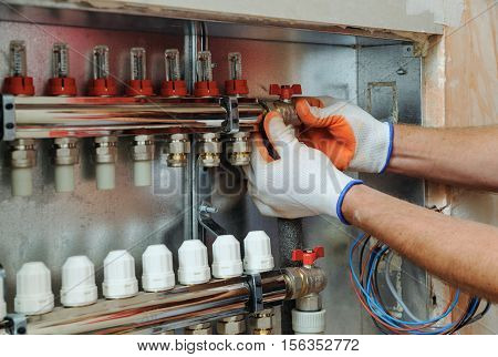 Installation of home heating. A worker attaches the tube to the collector heating. poster
