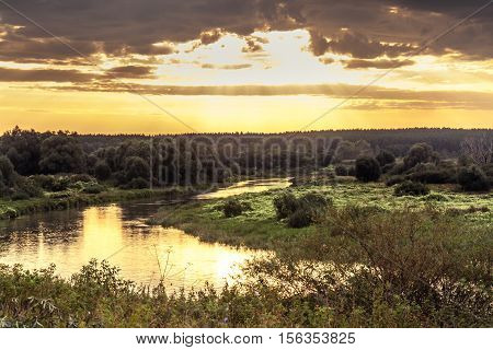 Vibrant sunrise with beautiful rural landscape at river bank with moody sky and sunlight