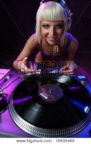 beautiful girl dj playing on vinyl player