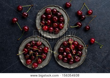 fresh cherry in vintage silver plate over dark grunge background, top view, close up