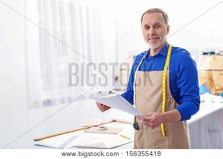 friendly tailor in an apron with papers looking into at camera