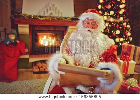 Santa Claus sitting next Christmas tree and reading children  wishes for Christmas