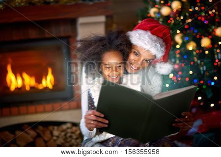 afro American mom and daughter enjoying in magic Christmas fairytales