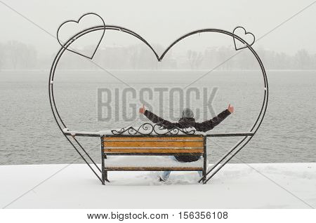 Unrecognizable man sitting on the beautiful wrought iron bench of love in the park with pond and enjoying beautiful winter day in solitude