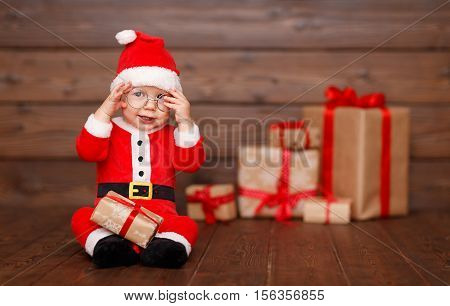 Happy baby in a Christmas costume Santa Claus with gifts on wooden background