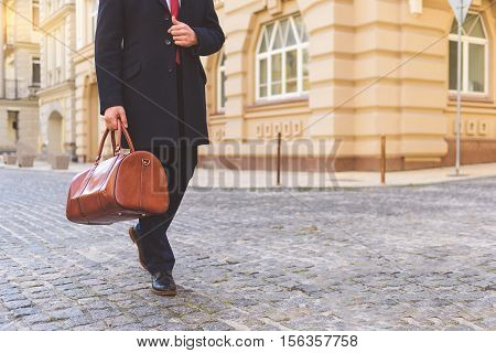Rich man walking on street and carrying briefcase