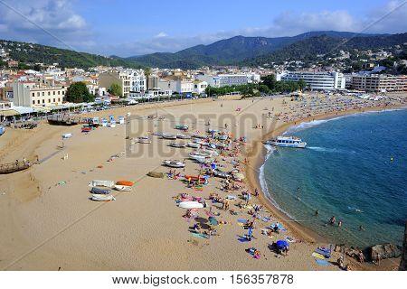 Tossa De Mar, Spain - August 1, 2014: Beach goers on the Tossa de Mar's beach