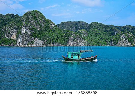Fishing boat in Halong Bay Vietnam Southeast Asia. UNESCO World Heritage Site. Beautiful scenery with sea and mountain at Ha Long Bay Vietnam. Most popular landmark tourist destination of Vietnam.