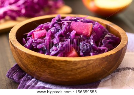 Braised red cabbage with apple in wooden bowl with ingredients in the back photographed with natural light (Selective Focus Focus in the middle of the dish)