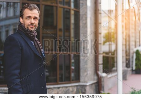 Relaxed man is breathing fresh air outdoors in city. He is standing and looking forward pensively