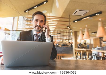 Happy senior man is deals with business by mobile phone. He is talking and smiling. Man is sitting at table in restaurant