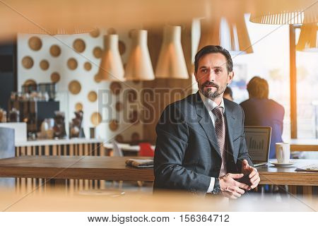 Dreamful businessman is sitting and relaxing in cafe. He is looking forward with anticipation and smiling. Guy is holding smartphone