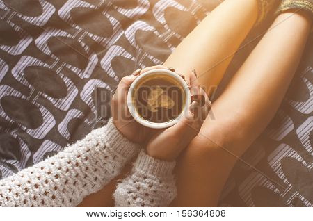 Detail of sexy young woman and sun light. Woman keep a coffee cup and read a book. She is sitting on a blanket.. Naked legs. Home atmosphere.