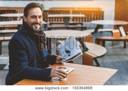 Happy middle-aged man is drinking coffee and reading newspaper. He is sitting at table in cafeteria outdoors and smiling. Man is looking at camera with joy