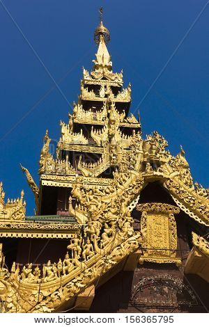 Beautiful buddhist temple with multiple storeys. It is golden and with beautiful wooden carvings. Shwedagon Paya area. Yangon, Myanmar