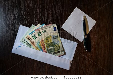 White envelope with Euro bills over wooden background