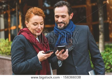 Middle-aged man and woman are exchanging phone numbers. They are standing on street and laughing