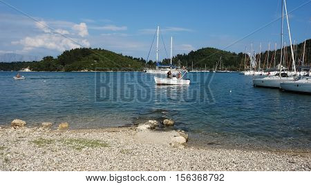 Nidri GREECE May 11 2013: Landscape with blue harbour green coast yachts and fishing-boat in Ionian sea Greece.