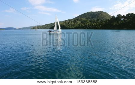 Lefkada GREECE May 11 2013: Panoramic view with green islands mountains and yacht in Ionian sea Greece.