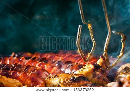 Sausage And Chicken In Barbecue With Tongs