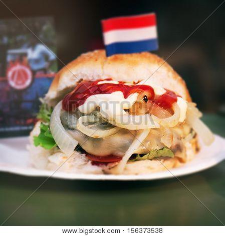 Dutch burger with fish herring onion and ketchup closeup