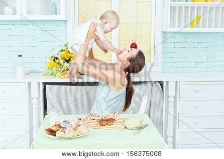 Mom plays with the baby in the kitchen.