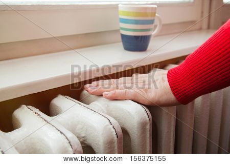 hand touching the radiator to check whether heated