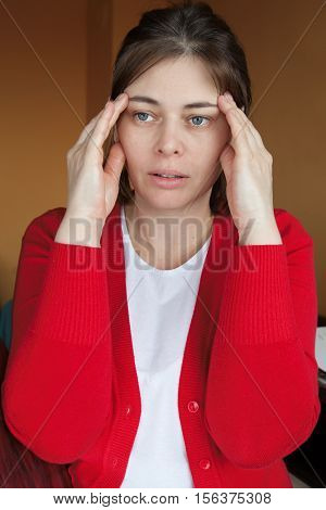a woman in her early forties dressed in a red blouse with a persistent headache