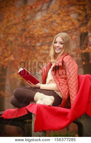 Smiling woman wearing jacket sitting on bench with book in park during fall