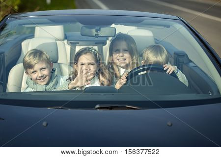 Cute four baby children friends of girls and boys people with at wheel pretends driving car as drivers on road outdoor
