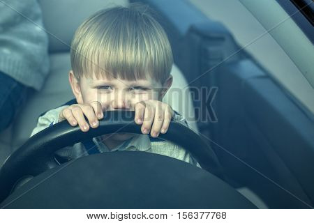 Cute baby boy child with blond hair at wheel pretends driving car as driver