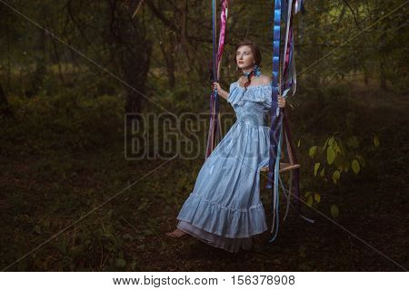 Fabulous retro woman in a smart dress in the woods sitting on a swing.