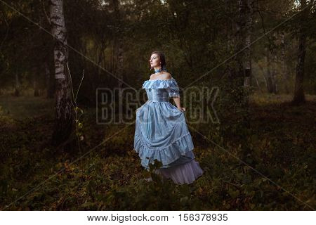 Girl in retro vintage dress walks through the woods like a fairy tale.