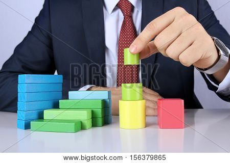 Business man builds diagram from wooden blocks bars.