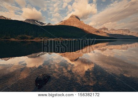 Waterfowl Lake sunrise with water reflection of mountains and cloud in Banff National Park