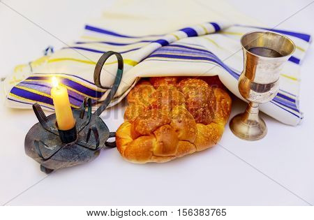 Jewish holiday shabbat image. challah bread shabbat wine and candelas on wooden table. glitter overlay