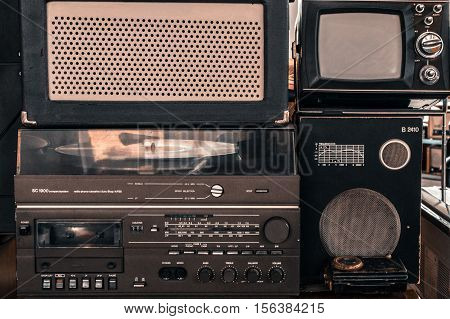 Old vintage audio system with radio, cassette tape recorder, record player, TV set, acoustic speakers