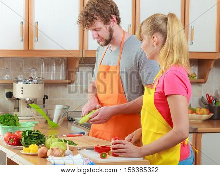 Healthy eating vegetarian food cooking weight loss and people concept. Happy young couple woman and man in kitchen at home preparing fresh vegetables salad meal